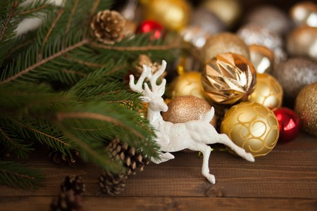 decorate: Christmas festive background with beautiful deer, golden balls and pine cons on wooden deck table