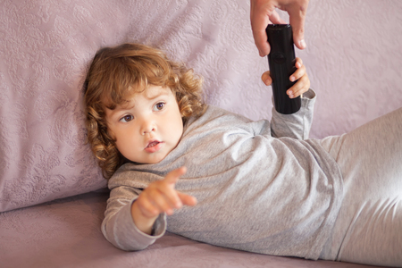 adult giving remote control to toddler kid, busy working parent concept, little girl watching tv Stock Photo
