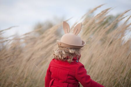 Toddler girl walking alone in the autumn field, wearing red coat and felt hat with binny ears. Cold blowy windy weather, sad mood, strong wind