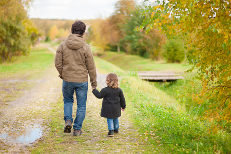 Father and daughter walking together in the park, fall day. Little girl and her dad exploring nature outdoors. Colorful autumn foliage. Copyspace. Archivio Fotografico