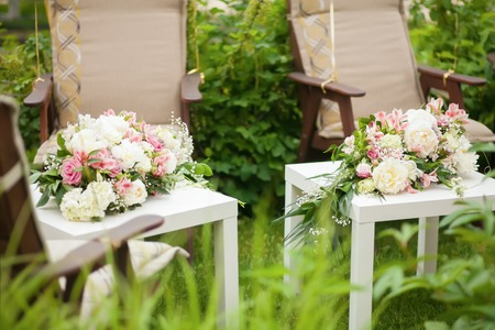 romantic places: Flower arrangement with pink and white roses and peonies, wedding day, outdoors.