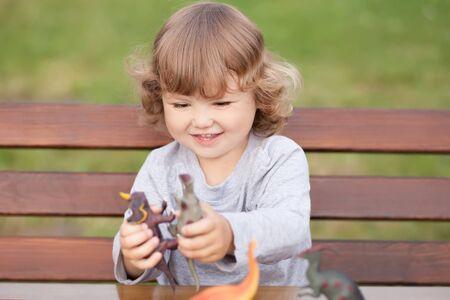 Meisje met plezier spelen in dinosaurussen vechten buitenshuis.