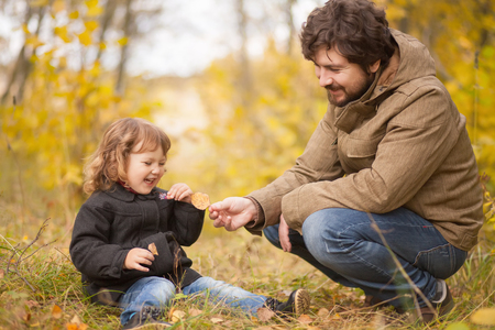 Father and his little daughter together in the wild forest, comunicating, playing, autumn day. Little kid exploring nature
