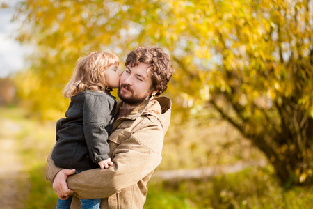 父と娘の秋の日は、公園を一緒に歩いています。少女は、彼女のお父さんにキスします。カラフルな紅葉。Copyspace