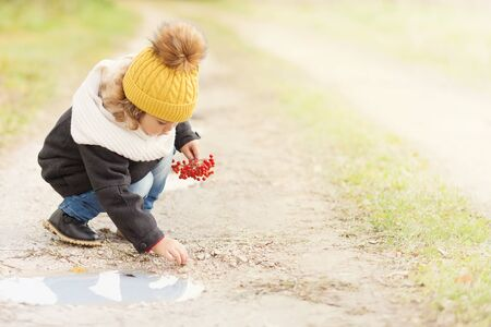 Cute toddler girl wearing black coat yellow knitted hat and scarf, outdoors, playing