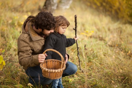 Father and child searching mushrooms in the wild forest, dad and kid friendship. Fall day. Little girl exploring nature