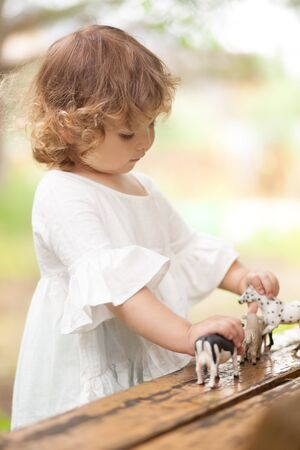 Cute toddler girl playing with farm animal figures outdoors. Summer leisure. childhood on countryside. Child learning farm animals. Early education and developement Stock Photo