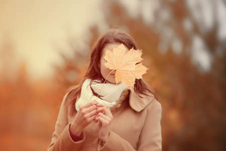 Cheerful woman hides face with autumn yellow maple leave, closeup