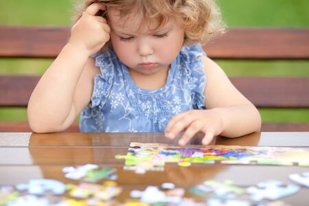 blonde unhappy toddler girl, solving puzzle on a table, hard difficult task. Early education and developement. Little genius concept. Emotional.