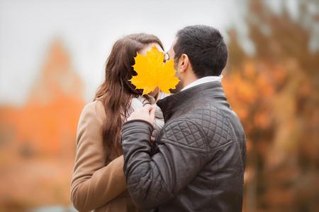 junges küssendes Paar, Gesichter mit gelbem Ahornlaub des Herbstes versteckend, geheimes Liebeskonzept