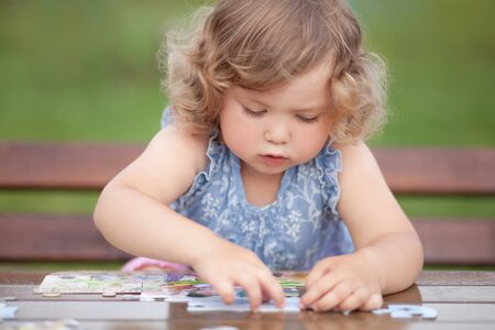 blonde toddler girl, solving puzzle on a table, having fun. Early education and developement. Little genius concept Stock Photo