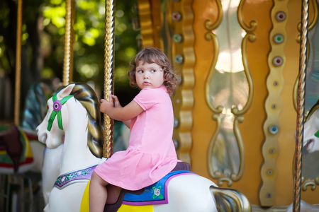cute little girl at the theme park, riding retro merry-go-round carousel Archivio Fotografico