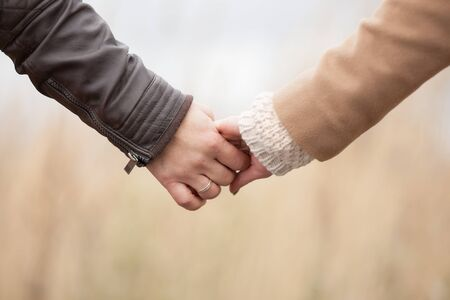 Closeup of loving couple holding hands while walking, married man, autumn background Stock Photo