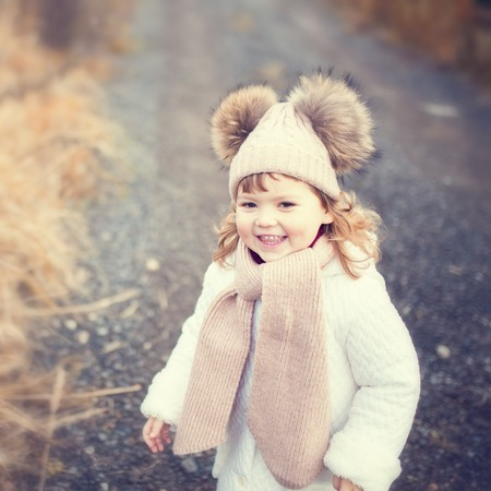 Autumn outdoor portrait of happy child girl, wearing warm white coat, scarf and hat, toned photo