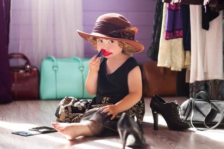 少女の身に着けている母親服イブニング ドレスとフェルトの帽子、母の化粧品でメイクアップを作るします。女性であることの学習
