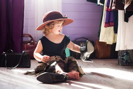 母親服のイブニングドレスを着て、帽子、女性の靴を感じた小さな女の子。女性になることを学ぶ。成長する概念