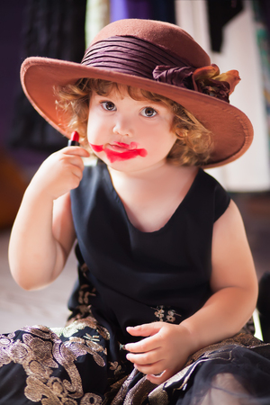 Little girl wearing mothers clothing evening dress and felt hat,  making make up with mother cosmetics. Learning to be a woman
