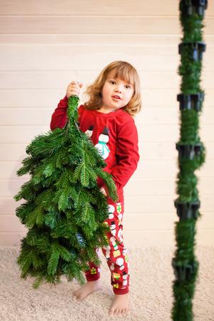 cute little girl assembling christmas tree indoors