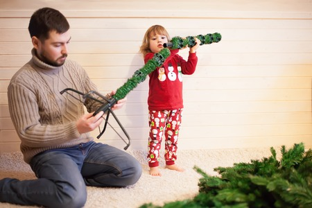 Father and daughter assembling christmas tree, smiling - christmas, holiday, winter concept, family activity