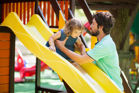Father play with his toddler daughter on a playground. Family leisure. Loving caring single father.