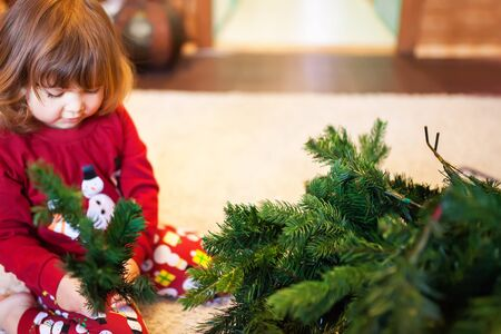 cute little girl assembling christmas tree indoors
