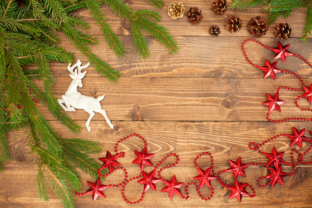Christmas festive background with beautiful deer, golden balls and pine cons on wooden deck table, toned photo.