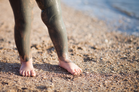Legs covered with black health mud, outdoors, closeup