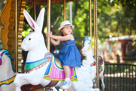 cute little girl at the theme park, riding retro merry-go-round carousel Stock Photo