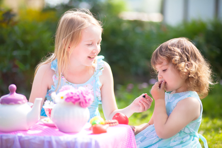 Adorable little sisters dressed like princesses playing tea party. Beautiful decorated tea party outdoors, at the backyard. 写真素材