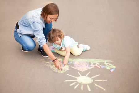 A little girl drawing on the asphalt with elder sister or nanny using colored chalks happily Archivio Fotografico