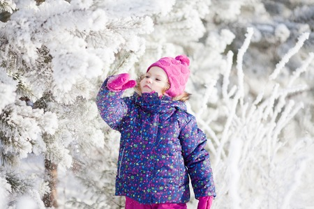 Cute toddler girl outdoors on a sunny winter day, walking, snowy day.