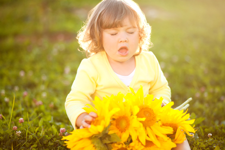 Cute little girl sneeze holding yellow sunflowers, outdoor portrait, allergy concept.