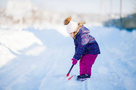 Little girl with a snow shovel, working outdoors, winter day.