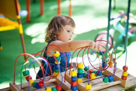 Little girl playing with educational toy - labyrinth. kindergarten concept, lifestyle. Early education and development. Stock Photo