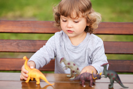 little girl having fun playing with plastic dinosaurs outdoors