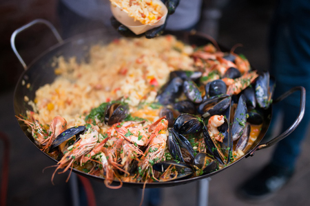 Chef making and cooking a traditional Spanish Valencian Paella with sea food in large pot, outdoors, catering, close up