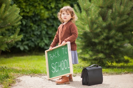 Cute caucasian little girl holding chalkboard written back to school. with a smile. ready and happy back to school. Fall outdoors, autumn day, education concept, back to school concept. Early developement, early education. Stock Photo