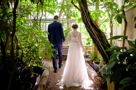 Bride and groom in the greenhouse with tropical plants, wearing beautiful vintage dress, close up