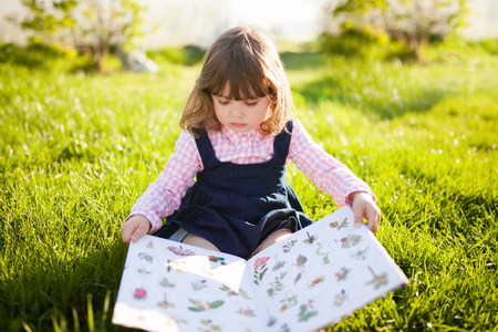 Moscow, Russia. 9 May, 2018. Adorable little girl reading botany book, learning nature in the garden. Early development education concept. Stok Fotoğraf