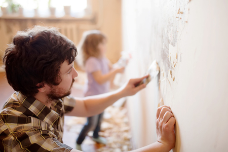 Father and daughter repairing wall, holding putty knife, family activity. Copy space