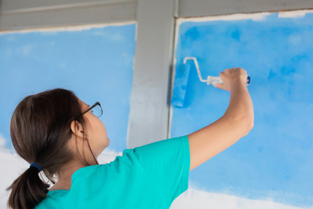 Young girl painting wall indoors with paint roller