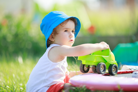 Cute blond curly little boy playing with big green truck outdoors, summer day