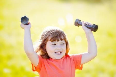 Happy little girl lifting dumbbells in the park. active healthy life. Fitness. Sport for little children. 版權商用圖片