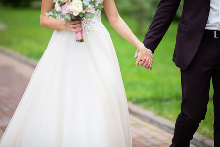 Close-up photo of married couple walk together outdoors, wedding day. Bride ant groom holding hands and walking together.