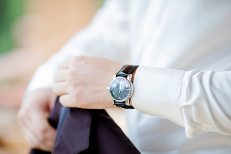 Businessman in white shirt checking time on his wristwatch. mens hand with a watch, close up. Groom preparing to wedding day
