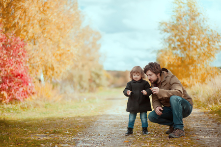 Father and daughter walking together in the park, fall day. Little girl and her dad exploring nature outdoors. Colorful autumn foliage. Copyspace. Imagens