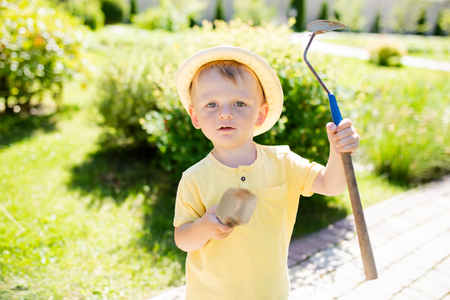Cute toddler boy wearing straw hat standing in the garden holding little shovel, ready to work. Stock Photo