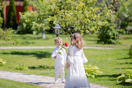 Adorable toddler boy and girl in angel costumes sitting together, boy giving red rose to the girl. Saint Valentines day. First love. Angelic children.