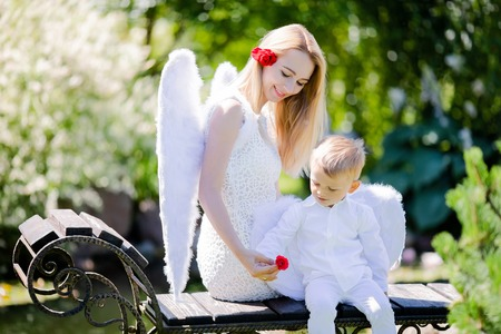 Beautiful mother and her toddler son wearing angel costumes. Cheerful moment, loving family. Mom is the Guardian angel for her child concept.