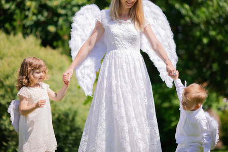 Beautiful mother and her toddler son and daughter wearing angel costumes. Cheerful moment, loving family. Mom is the Guardian angel for her children concept.